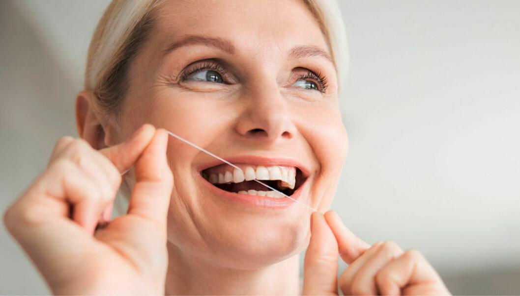 Kvinna gör rent mellan tänderna med tandtråd.