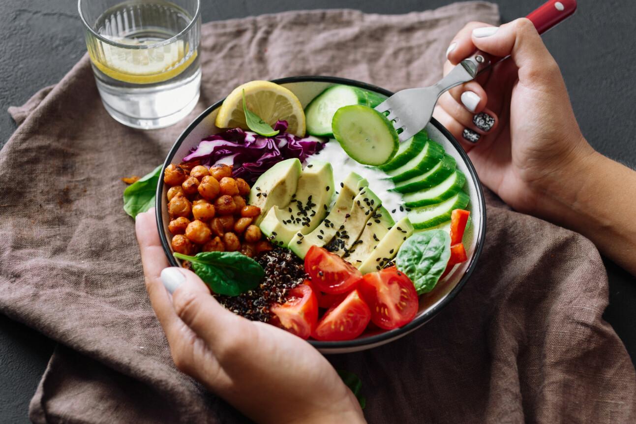Kvinna äter sallad ur djup tallrik.