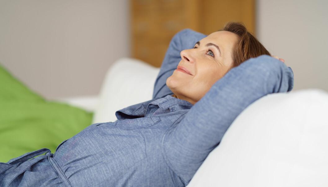 Kvinna kopplar av i soffa.