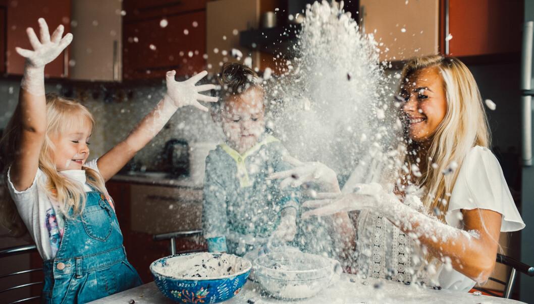 Kvinna bakar med sina barn och skvätter mjöl.
