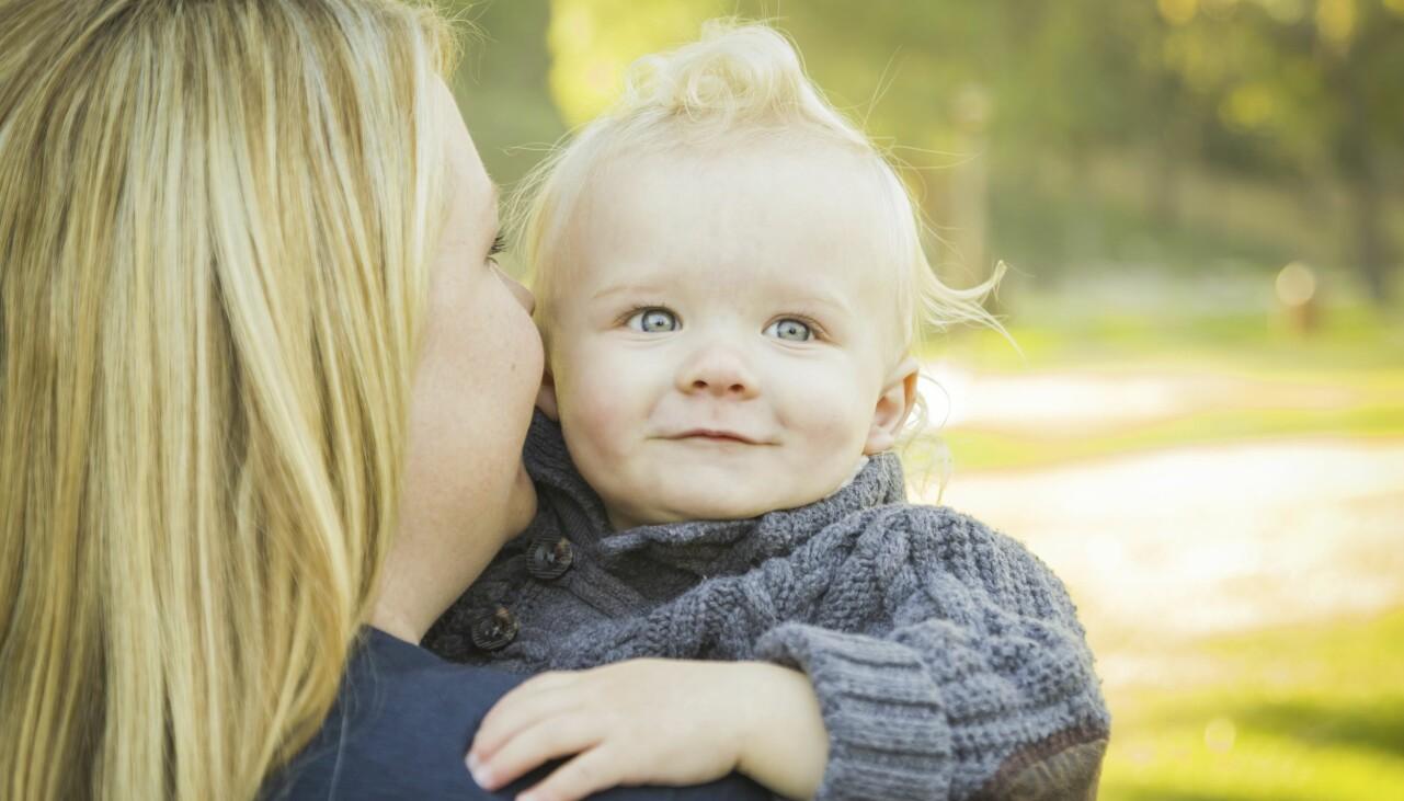 Kvinna bär ett litet barn i famnen.