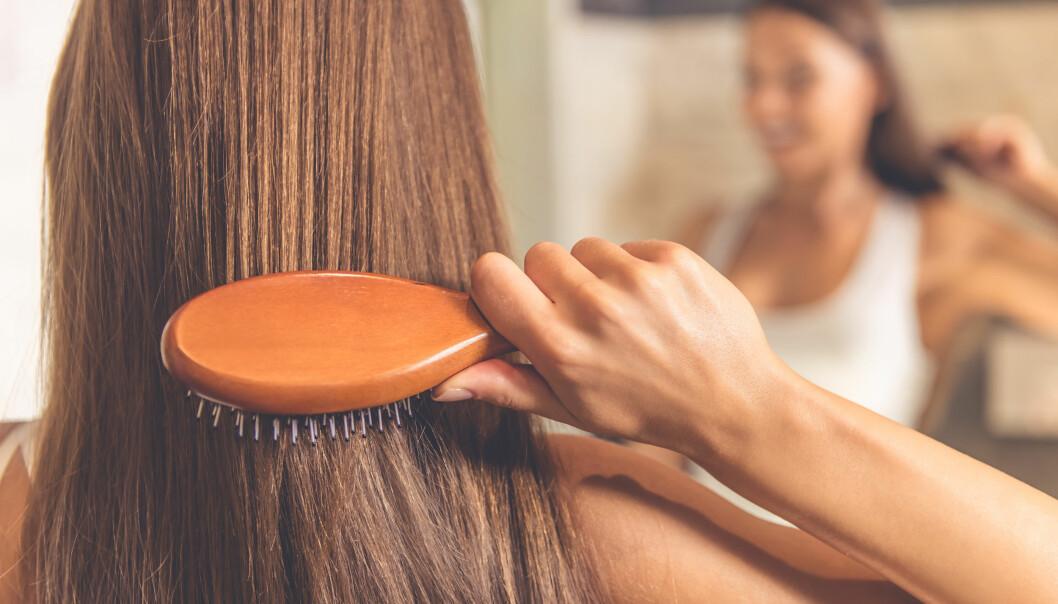Kvinna borstar håret framför en spegel.