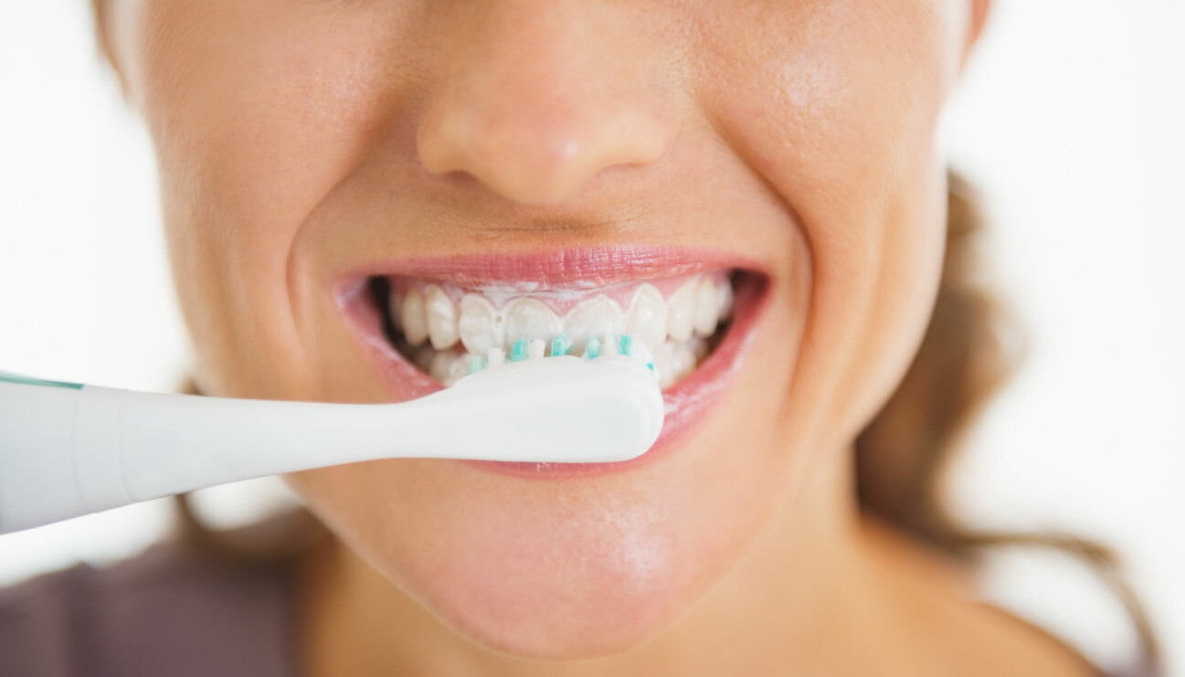 Kvinna borstar tänderna med tandborste.