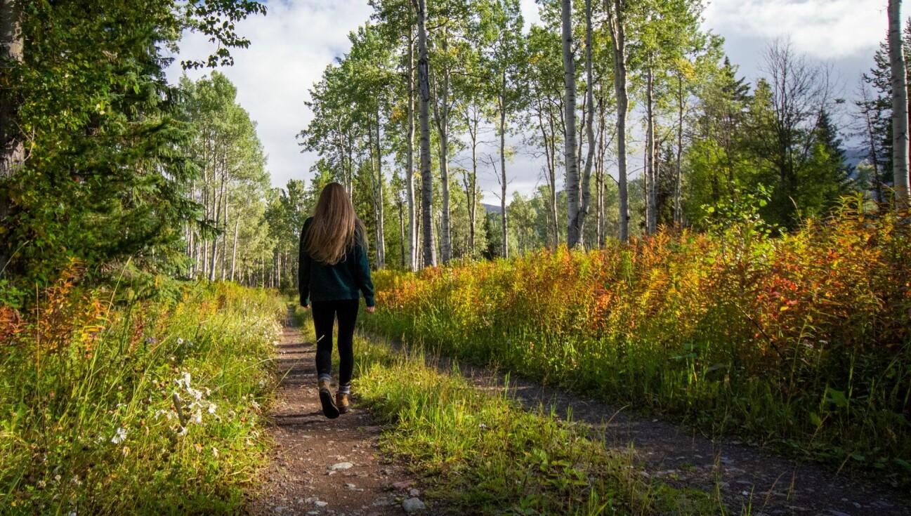 En kvinna går i lummig natur på en promenad som skyddar mot svår covid-19.