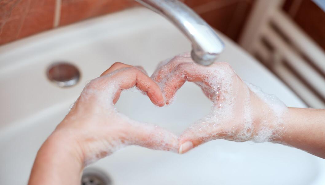 Kvinna formar ett hjärta med sina händer som är alldeles löddriga av tvål.
