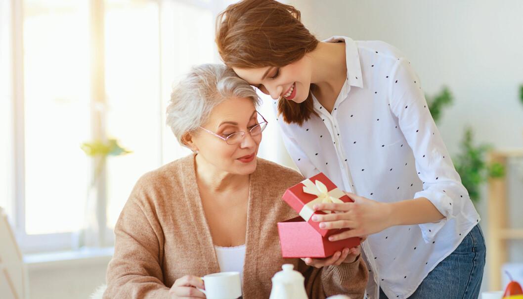 Kvinna ger present till äldre kvinna.