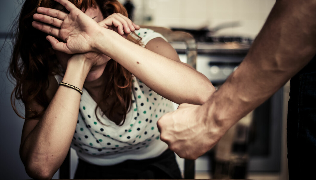 Kvinna håller upp händerna för att värja sig mot mannens knutna näve.
