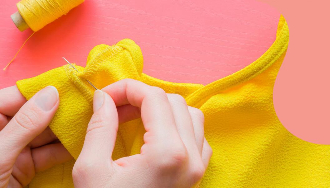 Kvinna syr med gul tråd i hul blus mot en rosa bakgrund.