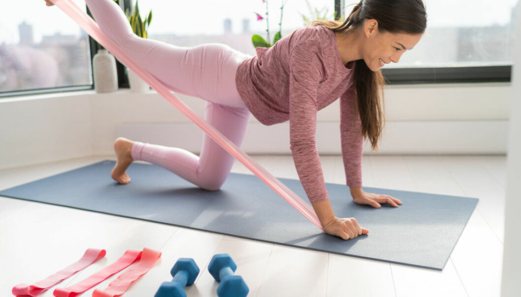 Kvinna i rosa träningskläder tränar hemma.