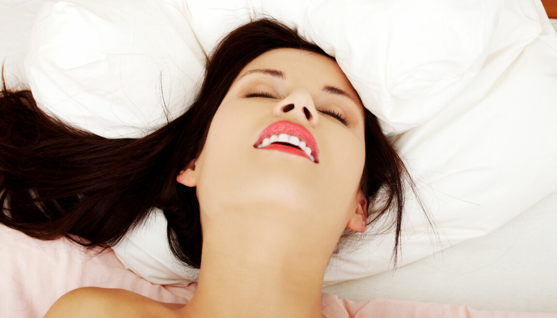 Kvinna i säng ser ut att få orgasm.
