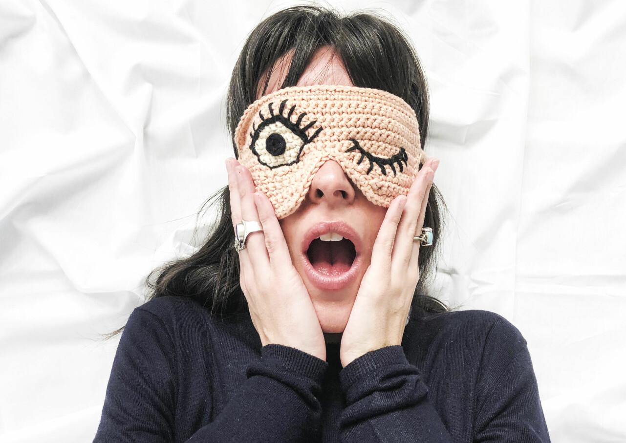 Kvinna i virkad sovmask med roligt mönster.