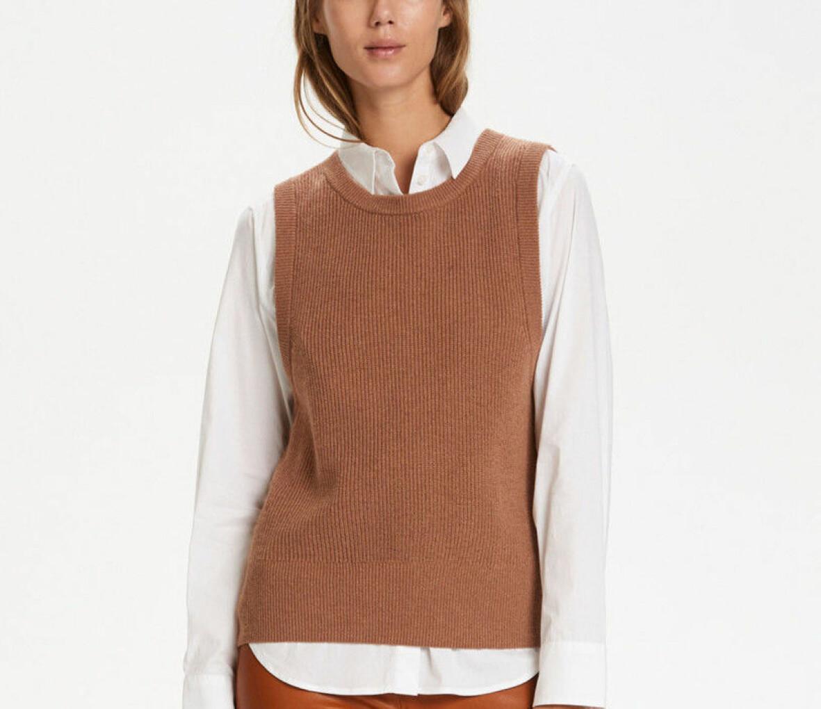 Kvinna i vit skjorta och brun väst.