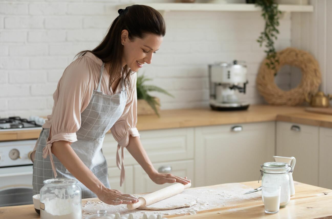 Kvinna kavlar ut deg i köket.