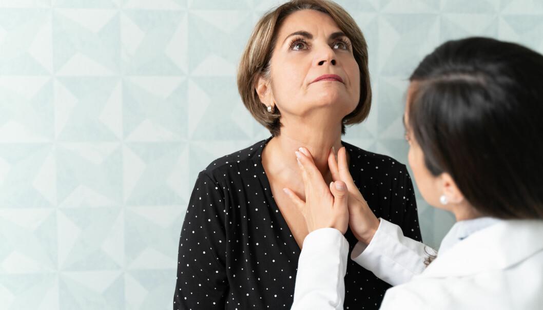 Kvinna kollar sin sköldkörtel hos doktorn.
