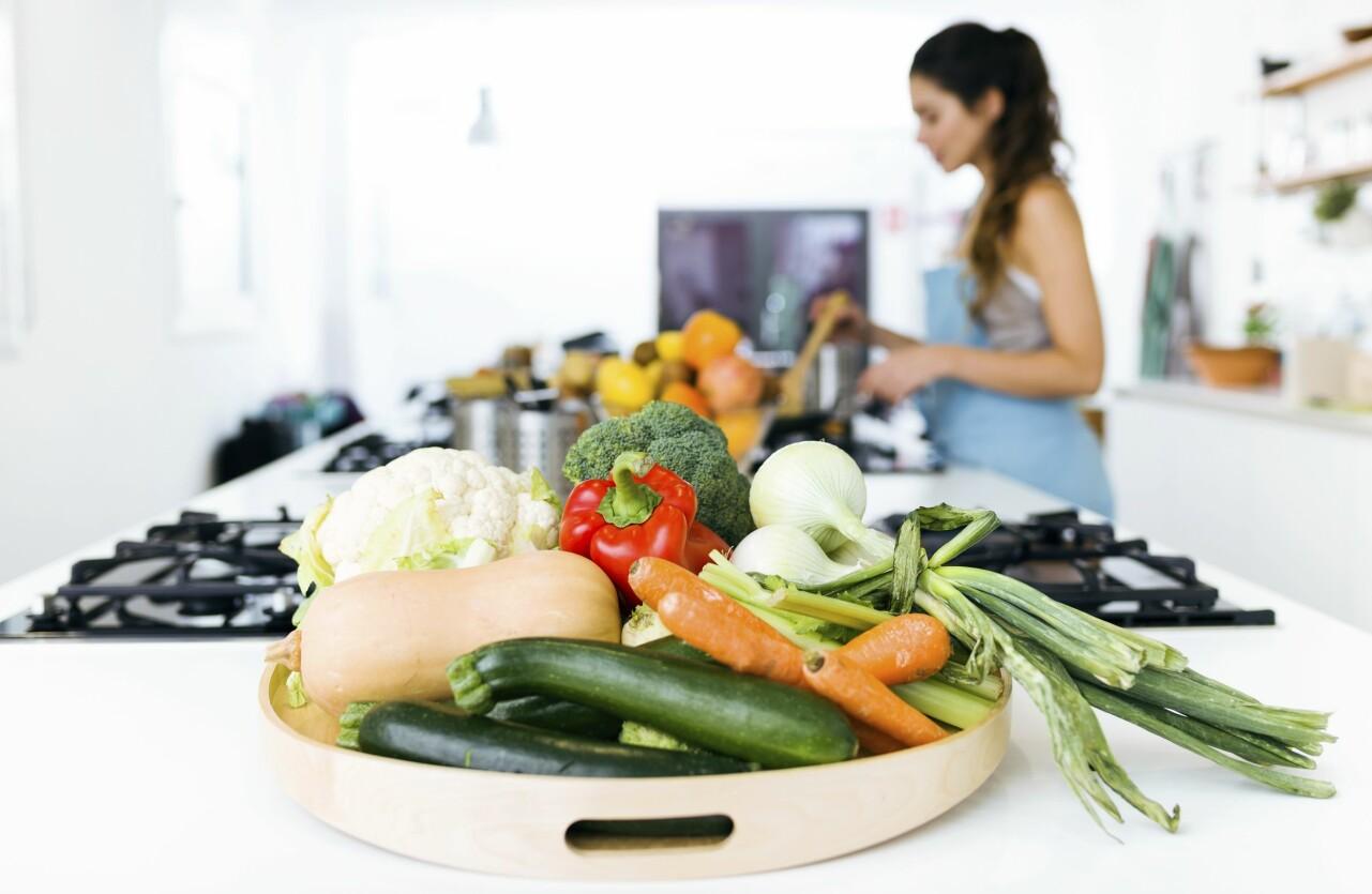 Kvinna lagar vitaminrik och nyttig mat.