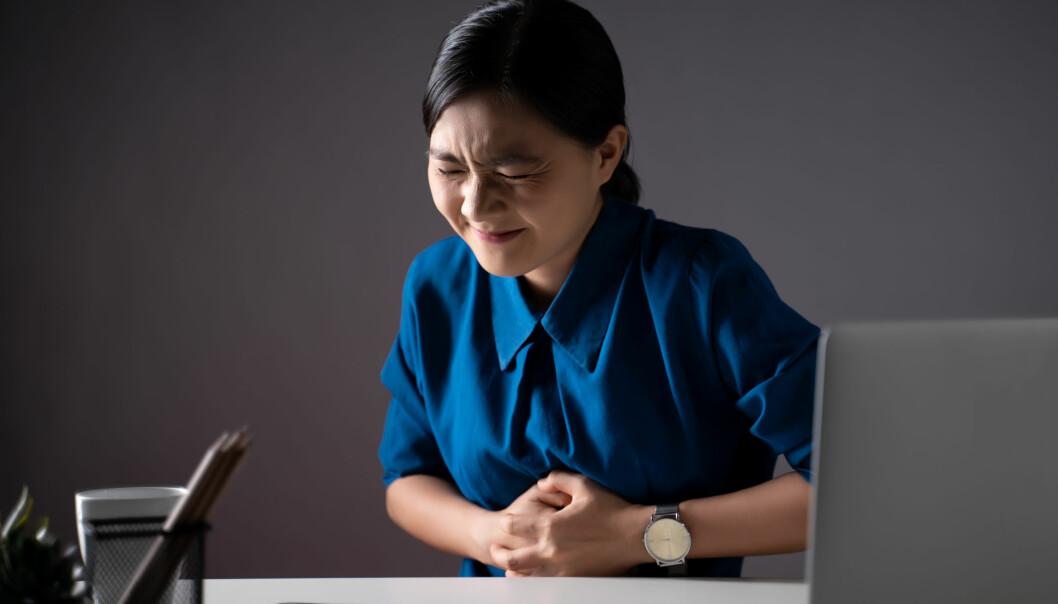 En kvinna som har fått ont i magen – ett symtom som kan tyda på magsår.