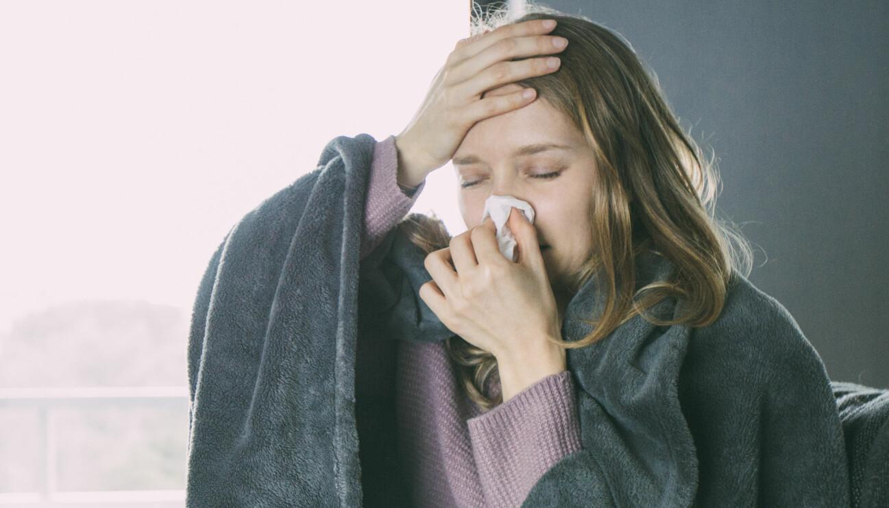 Kvinna med förkylningssymtom som snyter sig och håller sig för pannan.