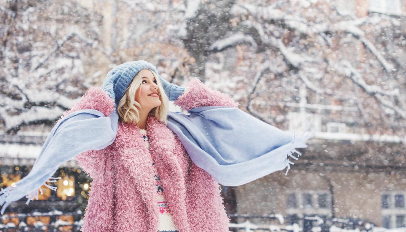 Kvinna med mössa i vinterlandskap.