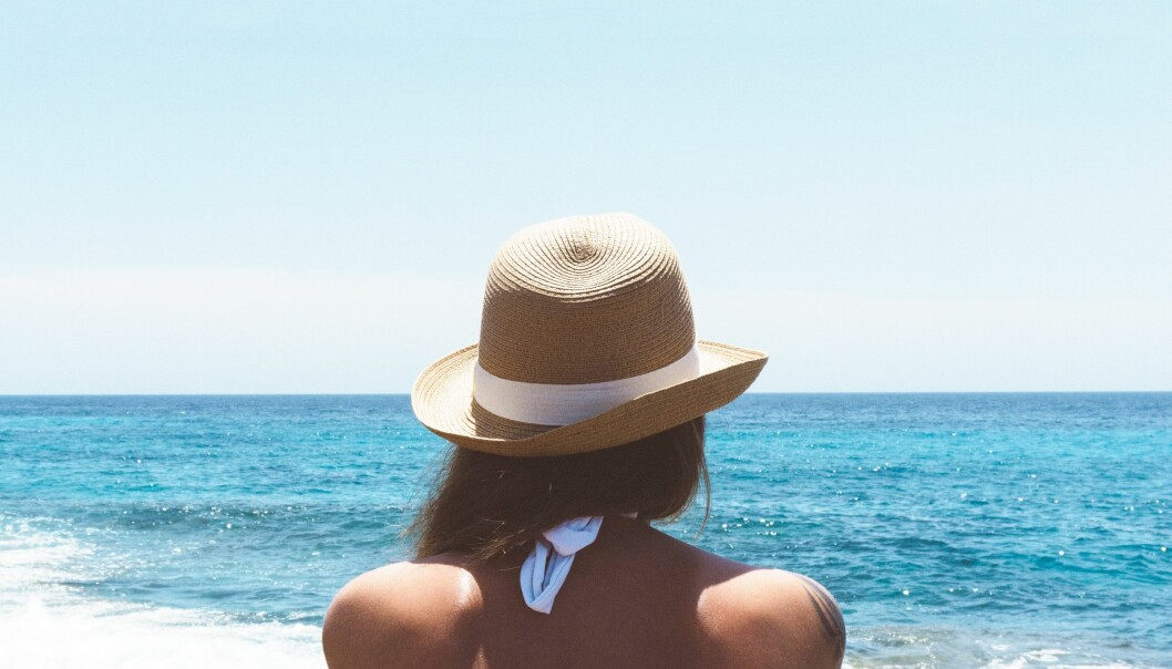 Kvinna med solhatt på stranden