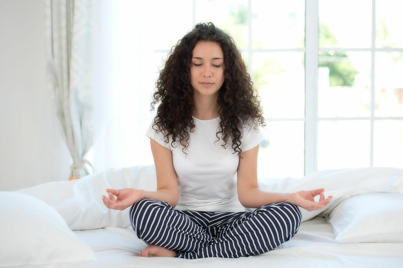Kvinna mediterar i sängen.