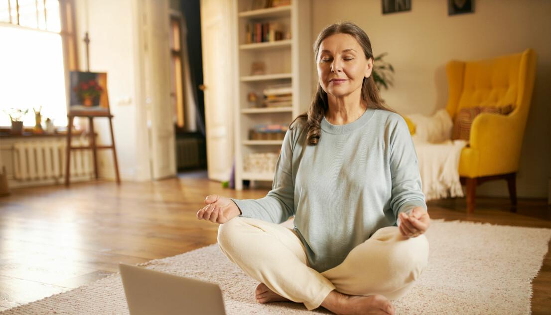 Kvinna mediterar och finner lugn genom att andas framför dator på matta hemma.