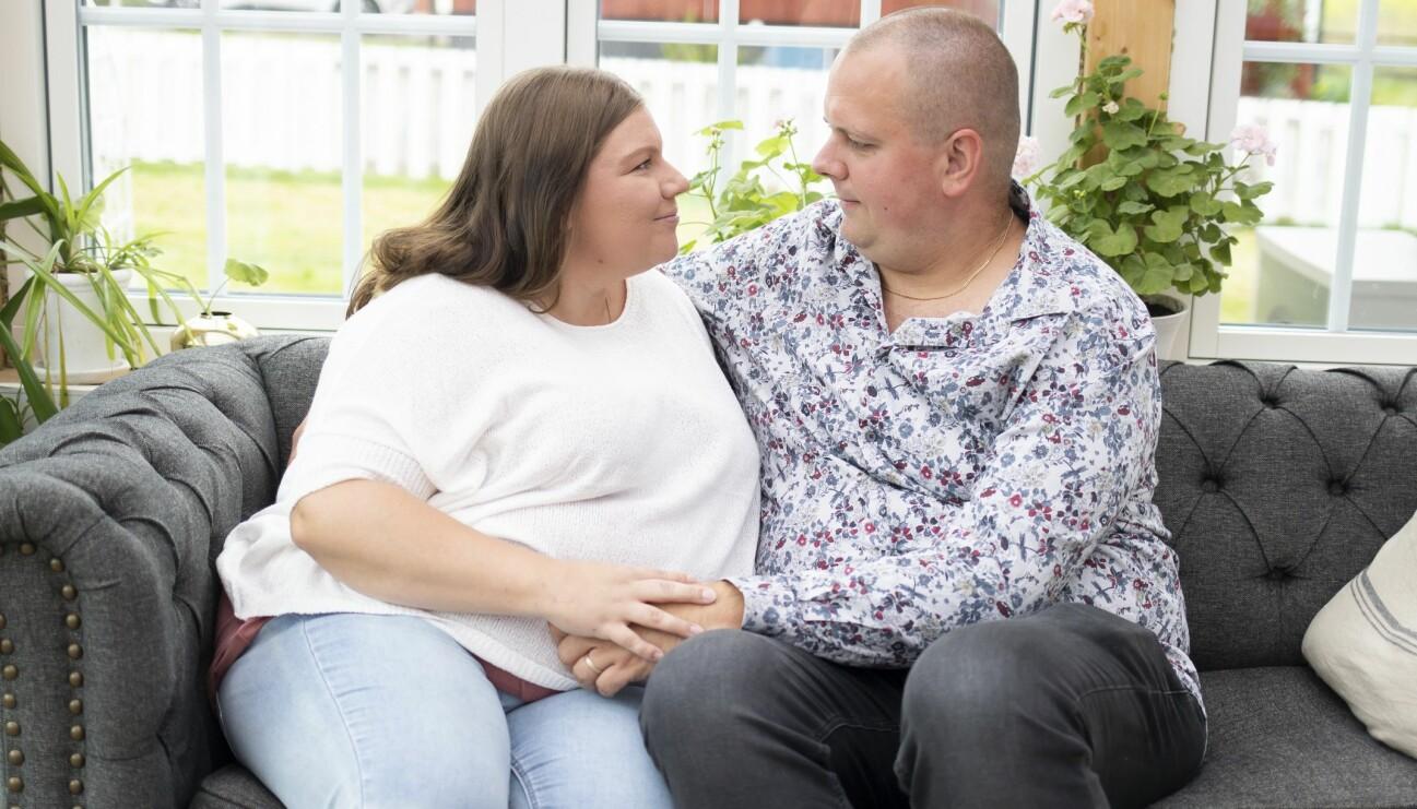 Kvinna och man håller om varandra i soffan.