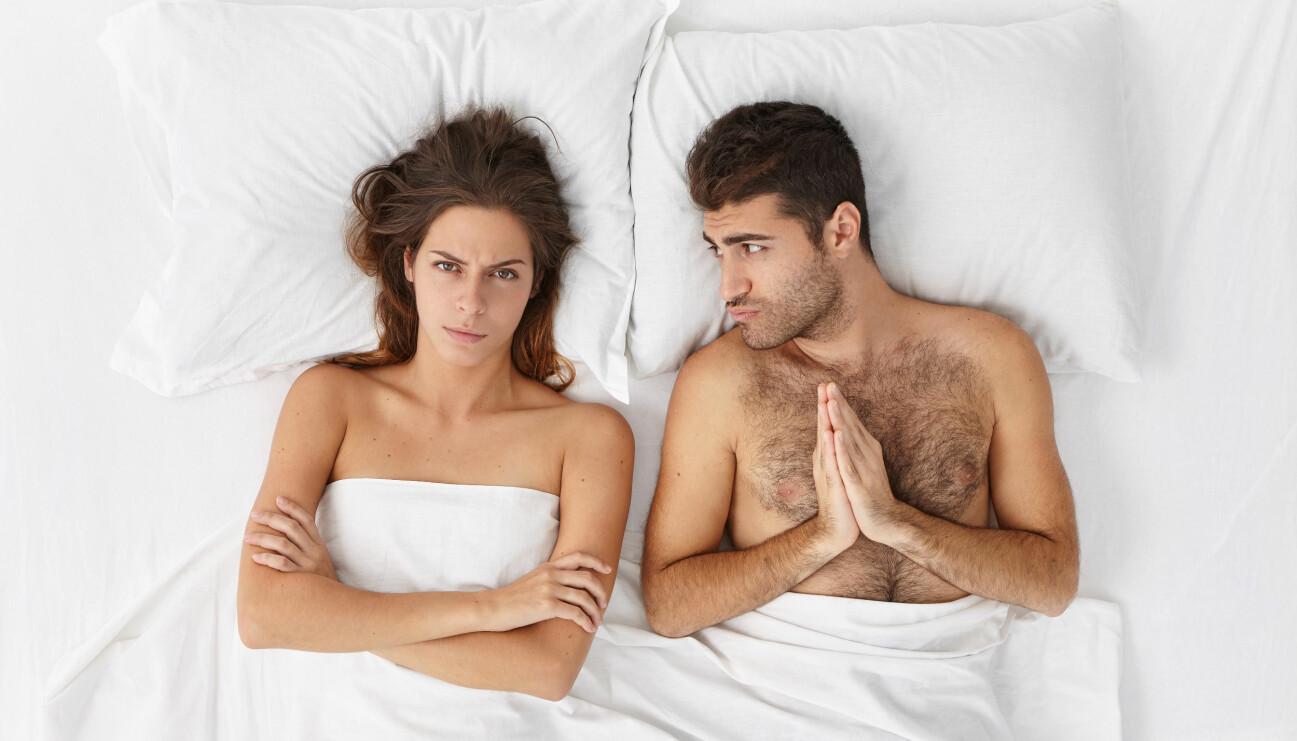 Kvinna och man ligger i en säng. Mannen ser bedjande ut.