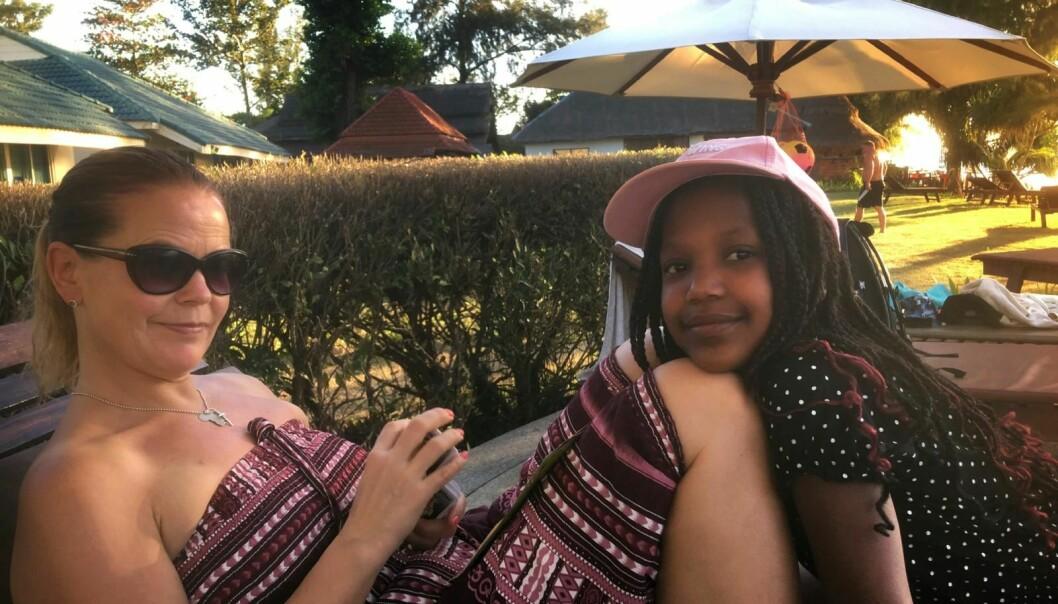 Kvinna och yngre flicka sitter i solstol.