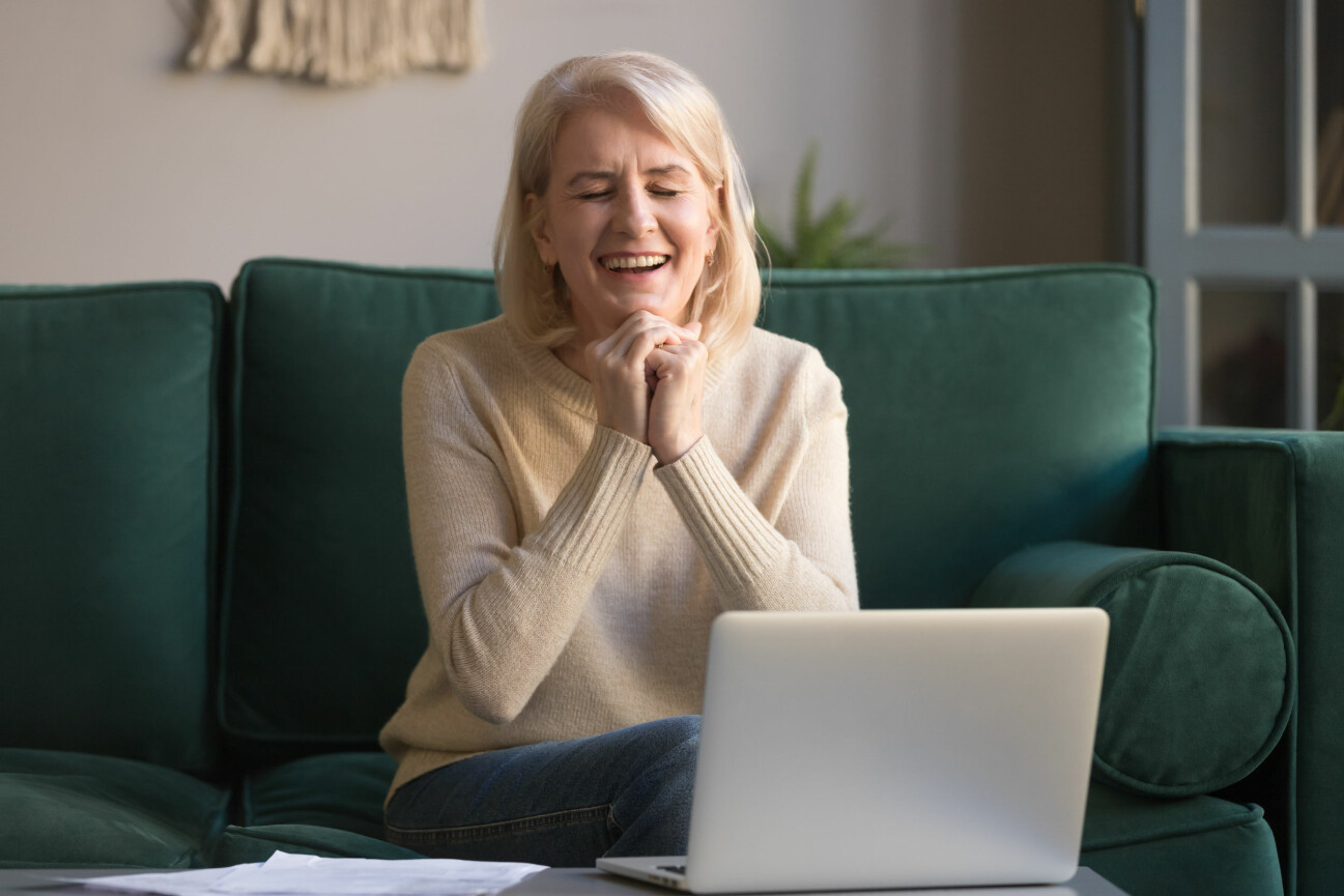 Kvinna på soffa skrattar.