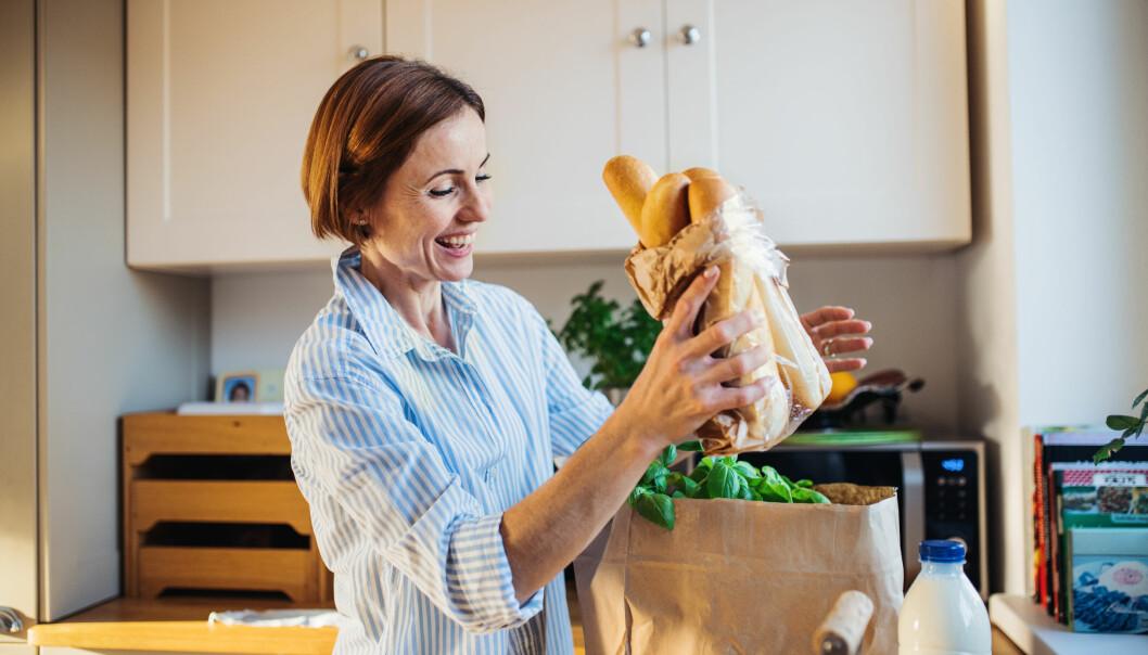 Kvinna packar upp matvaror i ett kök.