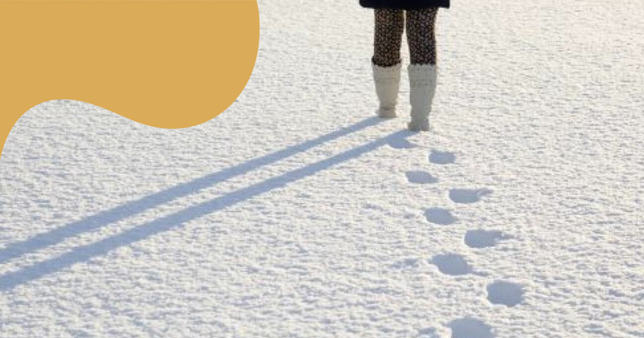 Kvinna promenerar i snön och lämnar spår efter sig.