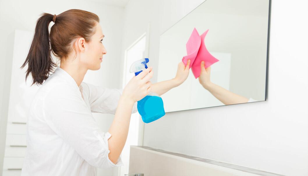 Kvinna putsar spegel med klassiska redskap.