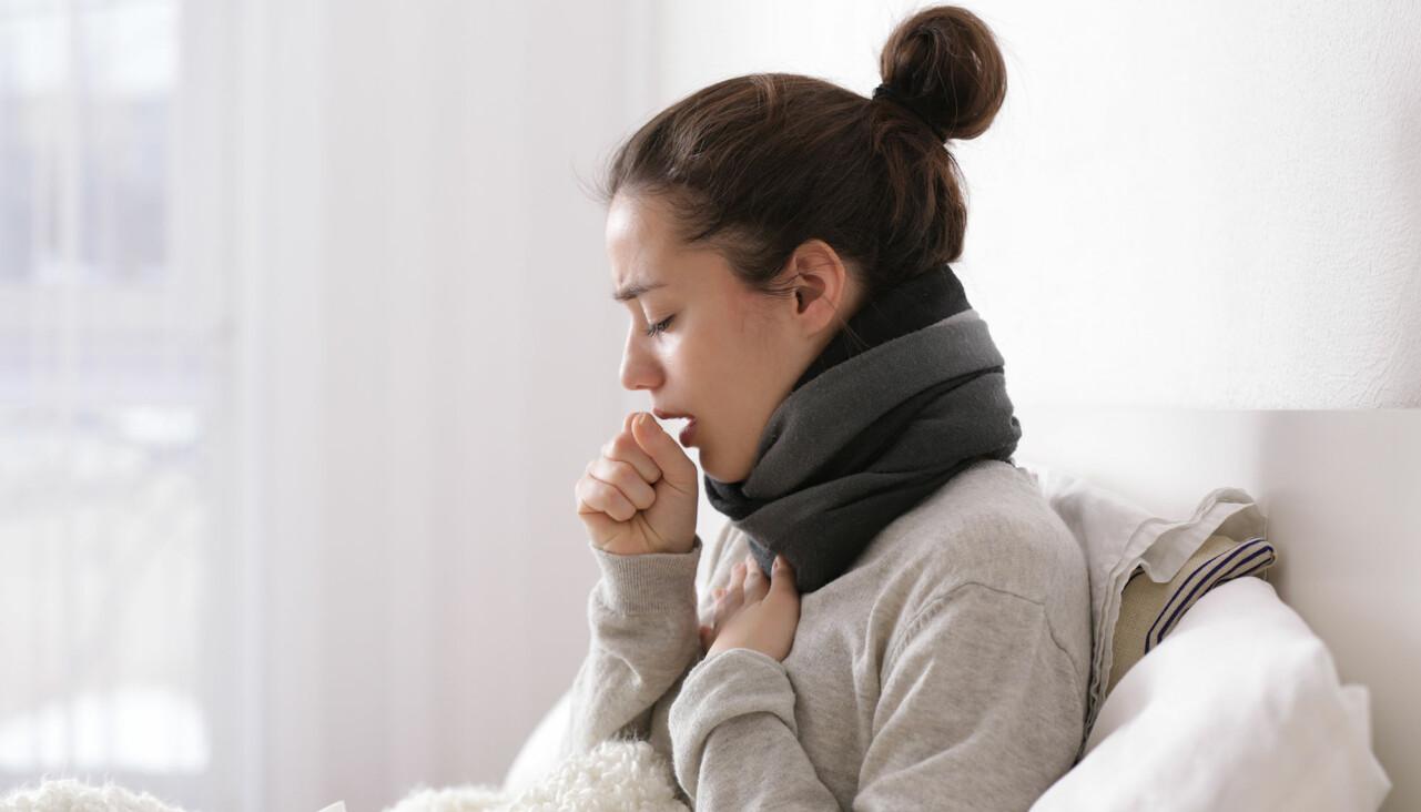 Kvinna sitter i en soffa och hostar.