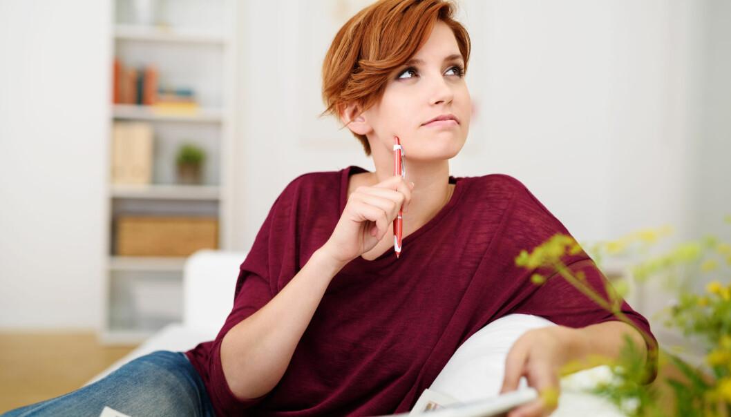 Kvinna sitter i en soffa och löser korsord.