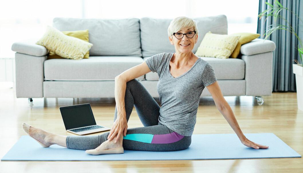 Kvinna sitter på golvet och tränar hemma