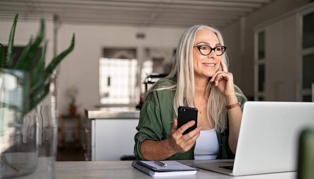 Kvinna sitter vid datorn med telefonen i handen och surfar.