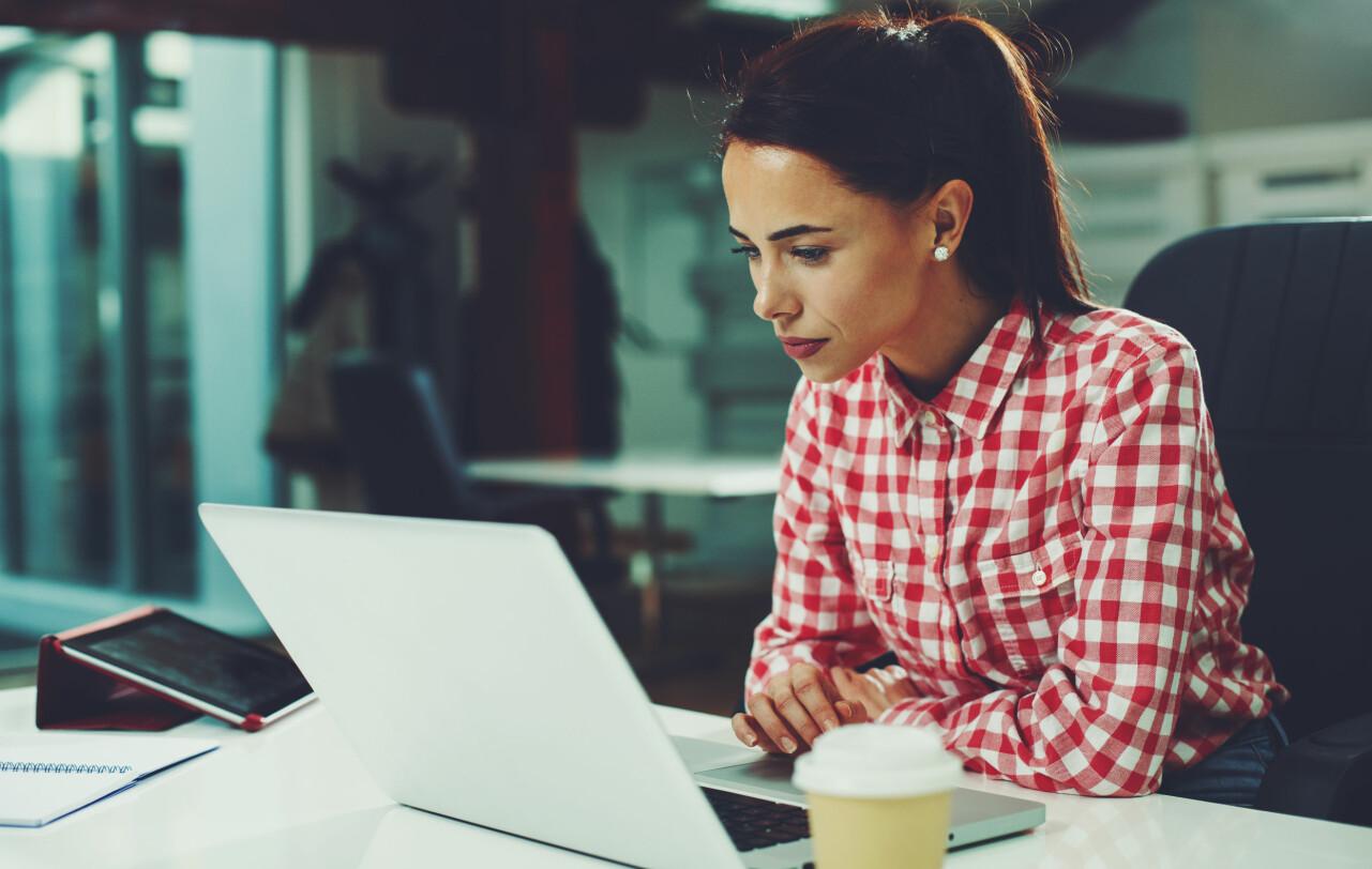 Kvinna sitter vid en dator och arbetar.