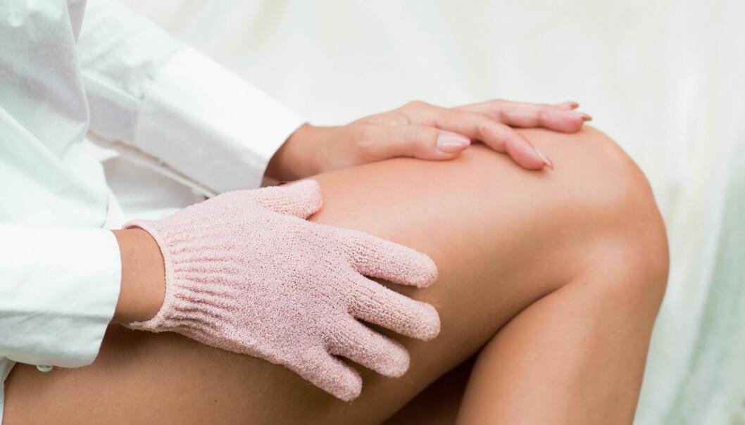 Kvinna skrubbar huden med en peelinghandske.