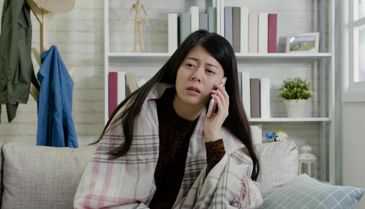 Kvinna som ser trött och hängig ut pratar i telefon.