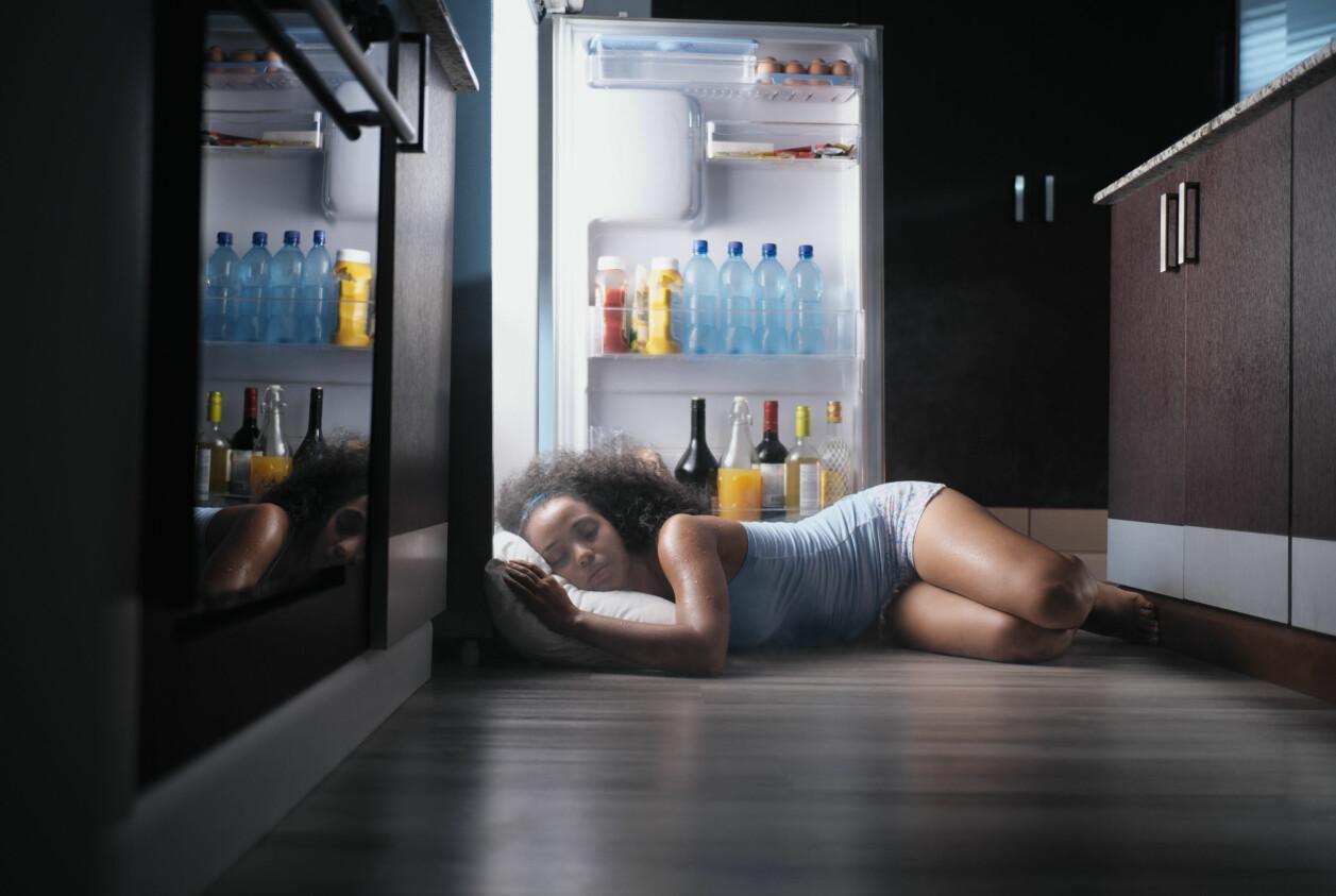 Kvinna sover vid öppet kylskåp på grund av värme.