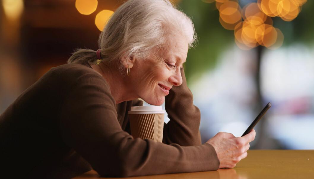 Kvinna Spelar spel på mobilen och dricker kaffe.
