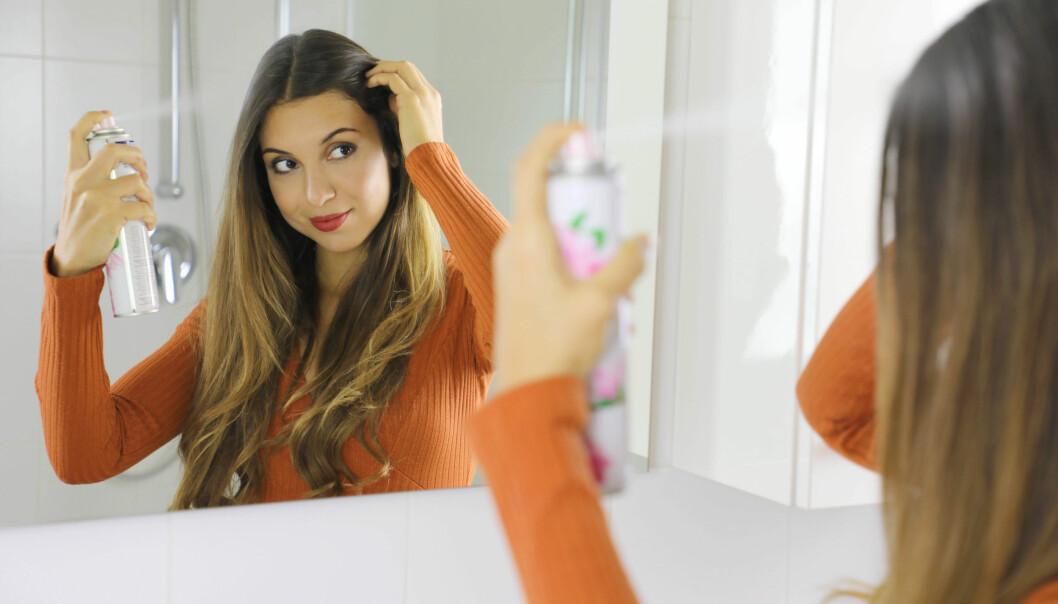Kvinna sprayar torrschampo i håret.