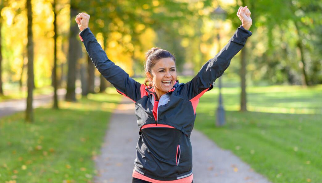 Kvinna springer utomhus med armarna i luften som en segergest.