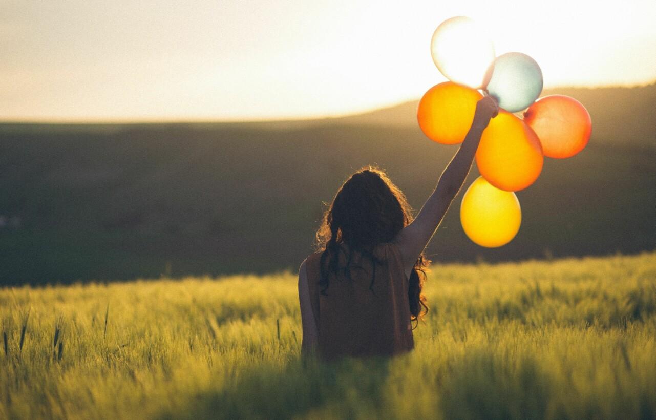 Kvinna står i grönt gräs och håller upp ett knippe färgglada ballonger i luften.