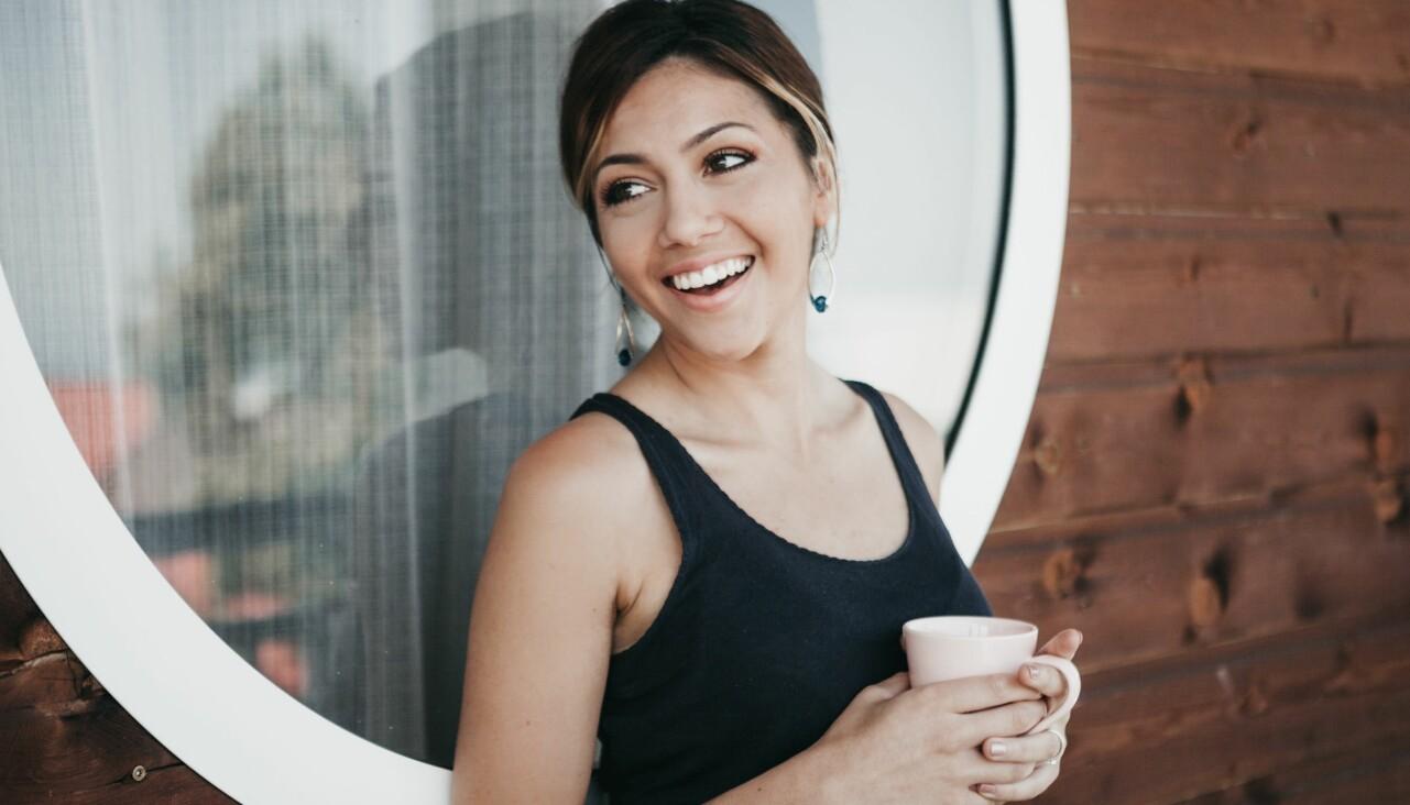 Kvinna står med en kopp kaffe i handen och ser avslappnad ut.
