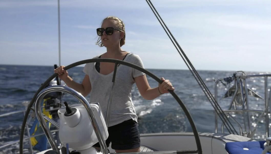 Kvinna styr en segelbåt.