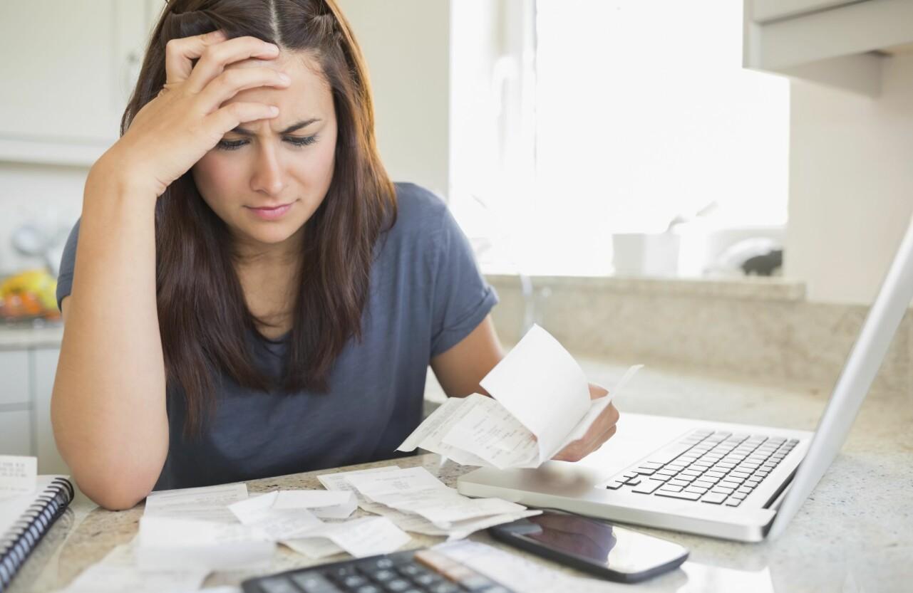 Kvinna tittar bekymrat på en hög med räkningar.