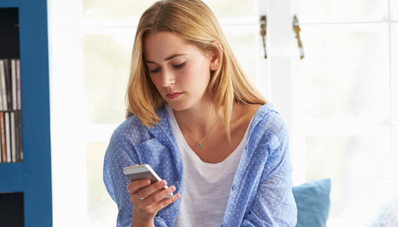Kvinna tittar förvirrat i sin telefon.