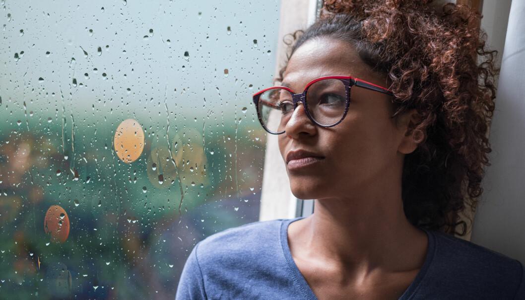 Kvinna tittar ut genom fönstret på regnet som faller utanför.