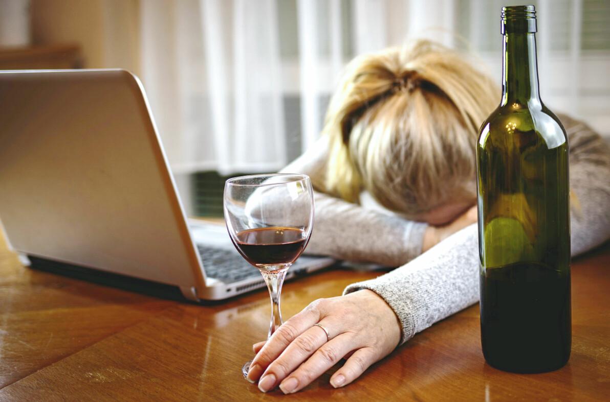 Kvinna utslagen framför datorn med vinglas och en flaska vin.